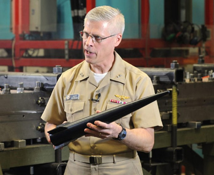 Rear Adm. Matthew Klunder, chief of naval research, shows the Hypervelocity Projectile (HVP). The next-generation projectile is designed as common, low drag, guided projectile capable of completing multiple missions for gun systems such as the Navy 5-inch, 155-mm, and future railguns. Photo: US Navy by John F. Williams.