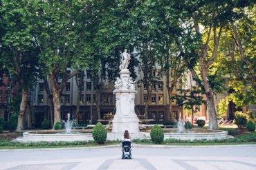 Pessoa em cadeira de rodas observando uma estátua em uma grande praça.