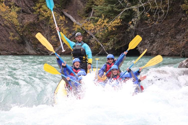 Des personnes dans un bateau de rafting levant les pagayes en l'air lors de la descente d'un rapide. (technique élaborées).