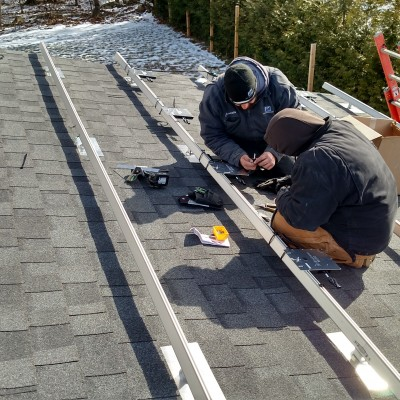 Two D/E/F Services Group electricians working on a residential photovoltaic install