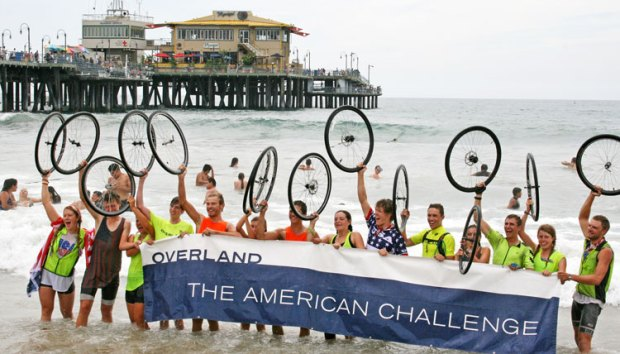 Henry Harris, center wearing the USA shirt in the middle of the picture, celebrates the successful cross-country bicycle adventure by dipping his back tire in the Pacific Ocean.