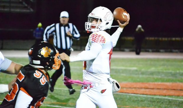Greenwich High School's Connor Langan throws the completion for a touchdown just behind getting taken down during Friday night's game against Ridgefield. (Paul Silverfarb photo)