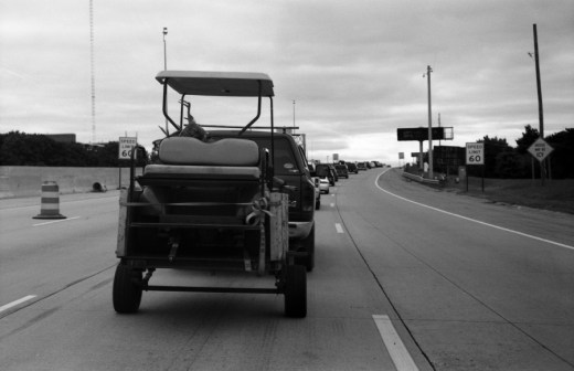 Took this on the highway on my way downtown, look carefully inside the golf kart.