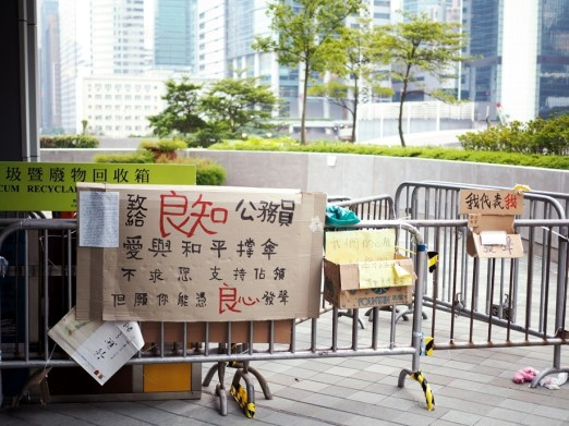 """One of the entrances to the government complex. """"To our government employees who know right from wrong: We are holding up our umbrellas with love and peace. We don't beg you to support """"occupy central""""; we hope you will speak from your conscience."""