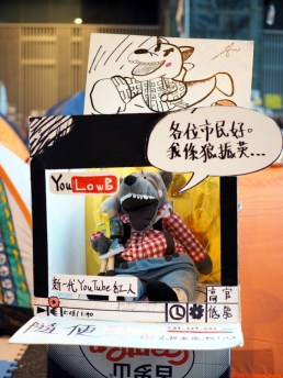 """A display mocking the Chief Executive. """"You Stupid"""" instead of Youtube. """"Hello citizens, I am CY Wolf"""" """"New Youtube hit""""""""High up government officials / Low Intelligence"""" instead of High and Low slogan."""