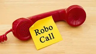 Getting a call from a Robocall, Retro red phone handset with a yellow sticky note and text Robocall