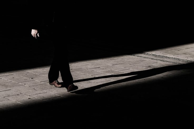 A man walking in the dark with some light shining in the middle