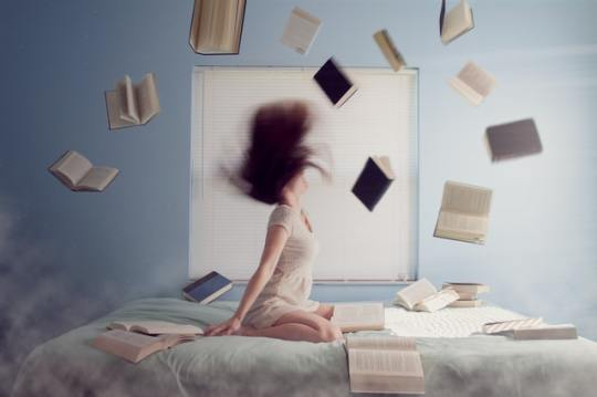 A woman throwing books