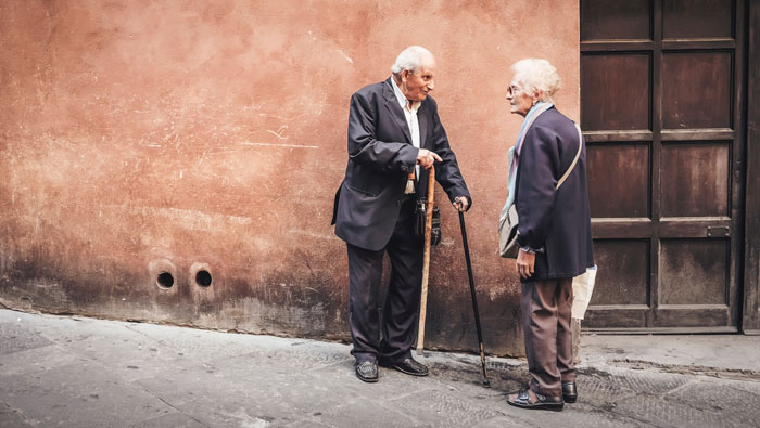 Zwei Senioren im Gespräch vor einer Mauer