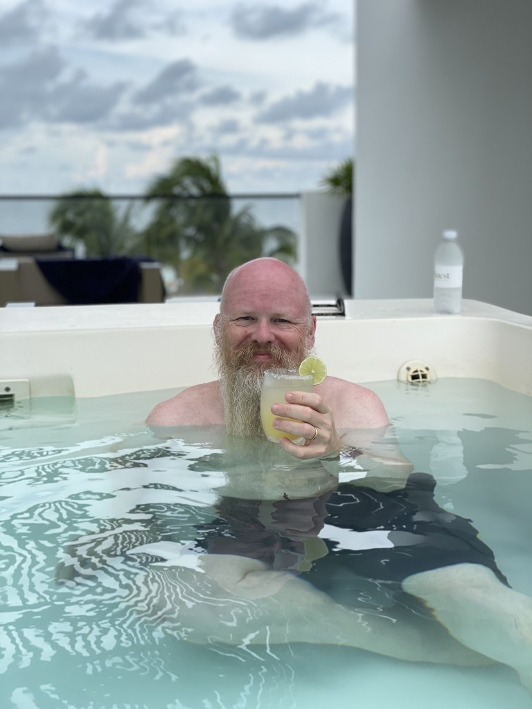 David enjoying a beverage in a pool