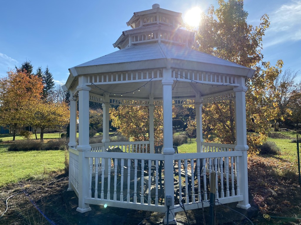 Sun peeking over the white gazebo