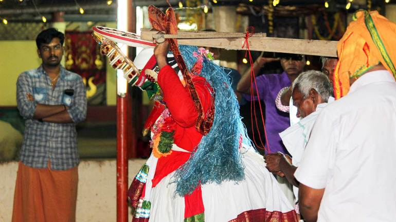Thookkam-performer-preparing-to-hang-on-the-stand-in-the-temple-yard