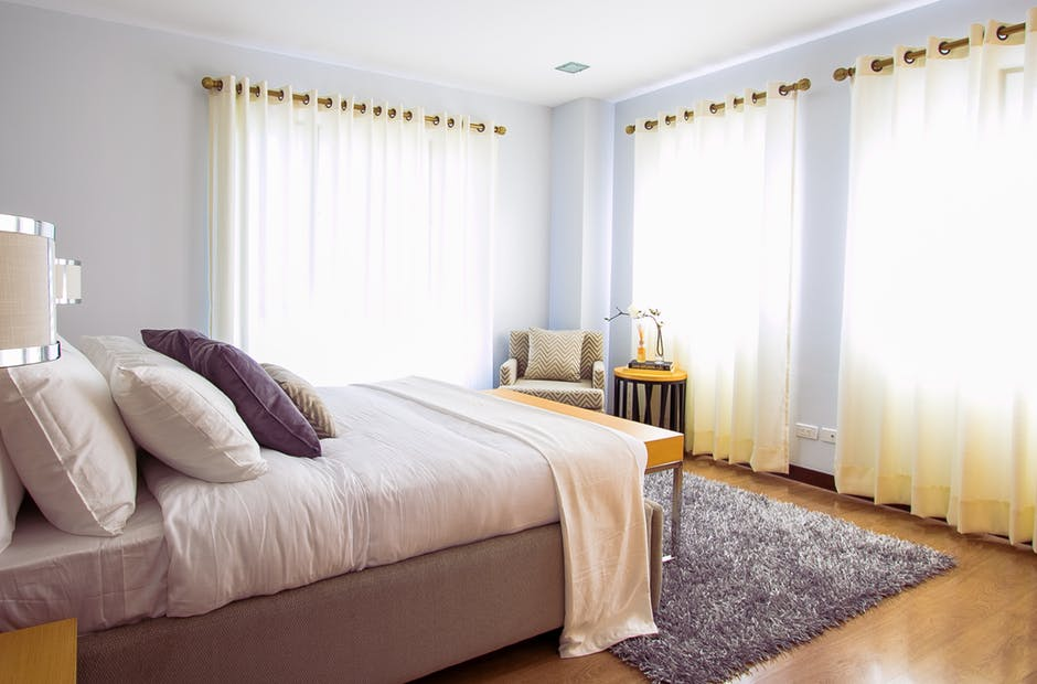 kamar tidur dengan satu kasur dan tiga gorden