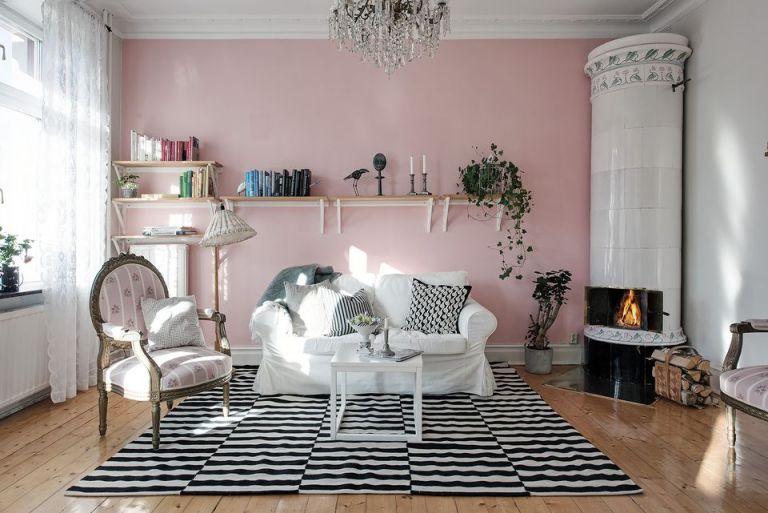 ruang tamu kecil dengan dinding warna pink dan karpet hitam putih