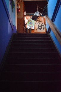 """After I was buzzed in, I was immediately greeted with a staircase atop which sat a handmade poster for """"The Loft""""."""