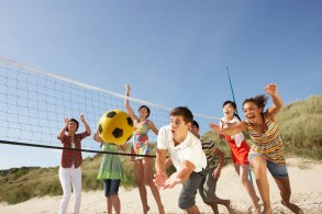 Group of teens playing beach volleyball