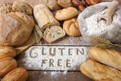 """The words """"gluten free"""" written in flour surrounded by loaves of bread"""