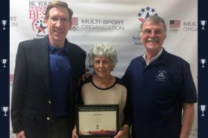 Georgia Billger was presented a Personal Best Award by National Senior Games Association CEO Marc T. Riker (left), along with Delaware Senior Olympics President Paul Gatti.