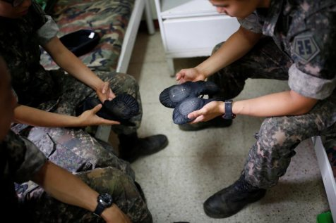 Soldiers examine the wear and tear on their ballet slippers after class | Kim Hong-Ji/Reuters
