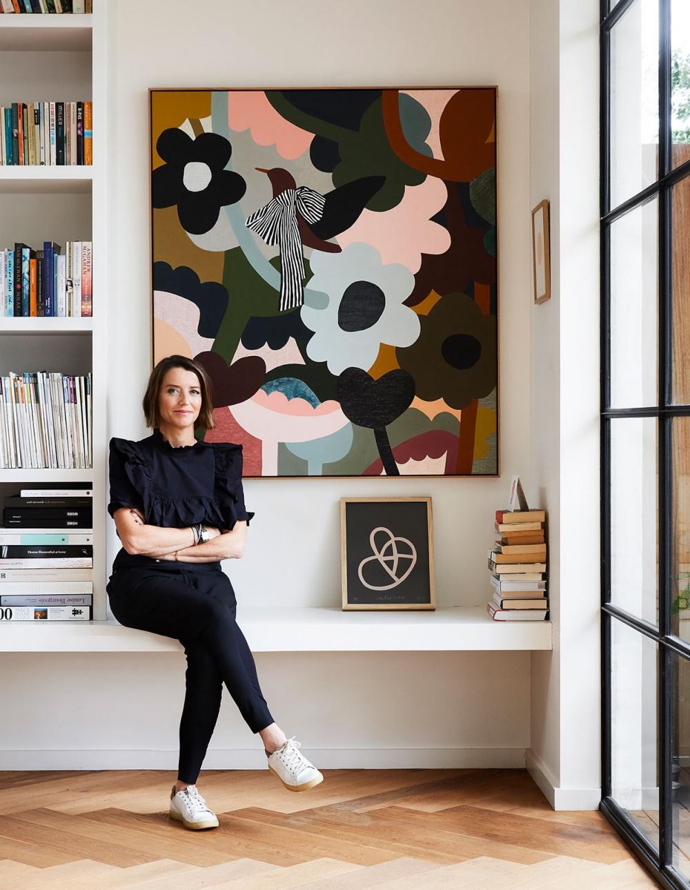 Rachel Castle la diseñadora australiana posando en la librería de su casa junto a una de sus obras