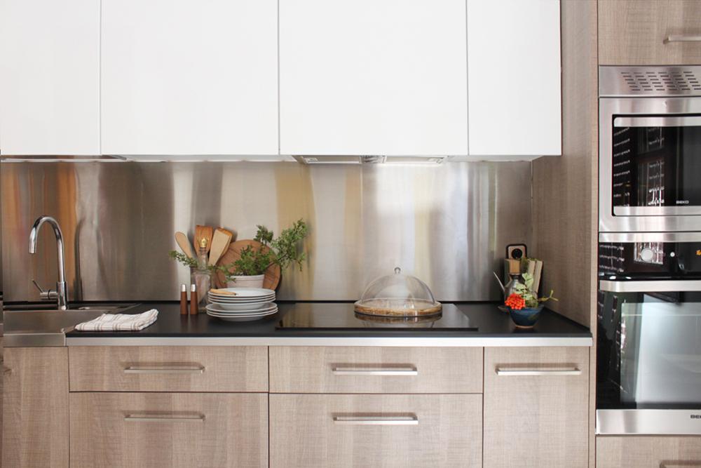 detalle de los muebles de una cocina combinando madera, acero y blanco