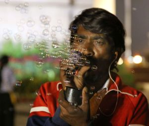 A toy vendor near India Gate blowing up soap bubbles