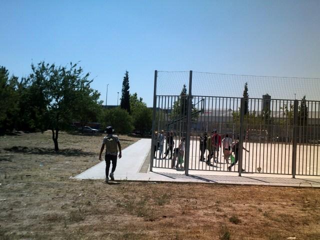 Personas llegando a la cancha de fútbol