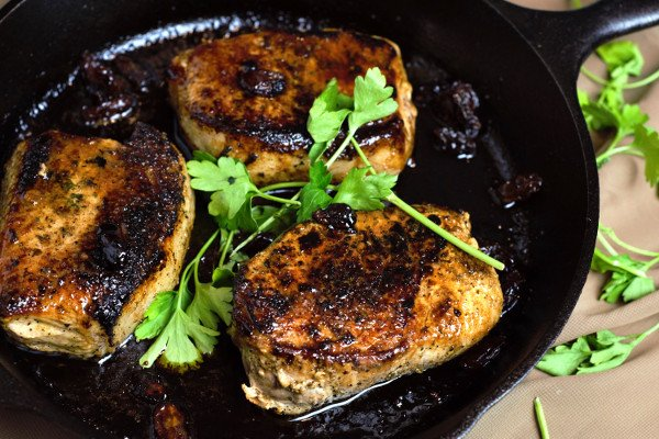Perfectly Glazed Pork chops in a cranberry, butter, and balsamic sauce.
