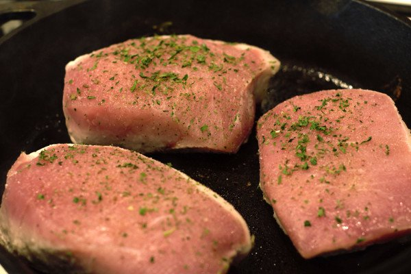 "1.5"" This Center Loin chops seasoned and placed in a hot cast iron pan."