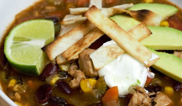 Beautiful Bowl of Chicken tortilla Soup filled with beans, corn, tomatoes, chicken topped with crispy tortilla strips.