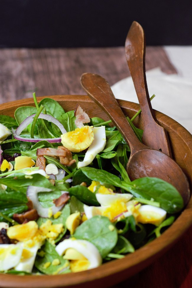 close up of spinach salad with wooden salad bowl and wood serving tools