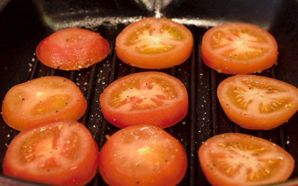Tomato slices on a grill pan lightly brushed with olive oil and seasoned with salt and pepper.