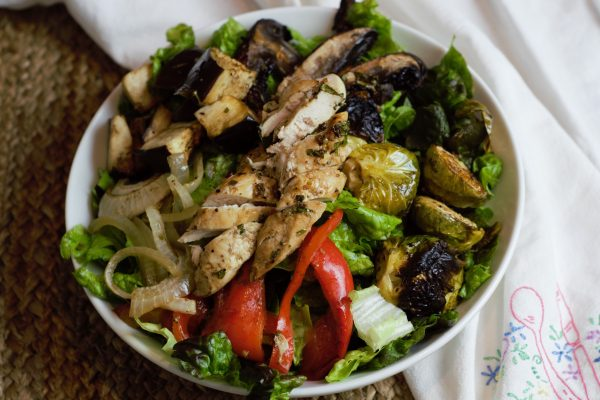 balsamic chicken over roasted vegetables in white bowl