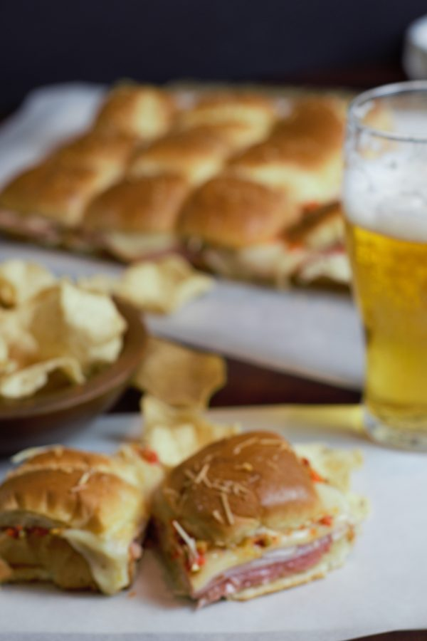 Italian Sub sliders served with a glass of beer and chips.