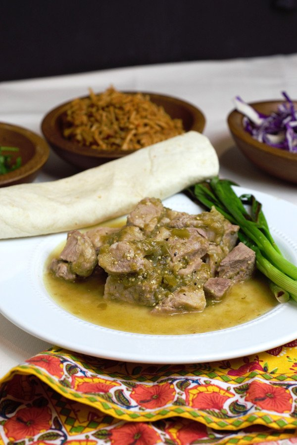 A huge plate of Tender Pork Chili Verde served alongside a warm tortilla and grilled green onions.