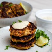 A Beautiful Stack of Salmon Cakes topped with Tangy Remoulade ready to enjoy.