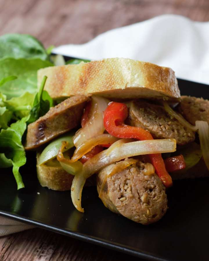 black plate with sausage and pepper sandwich