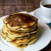 stack of pancakes on white plate with cup of coffee and glass of orange juice