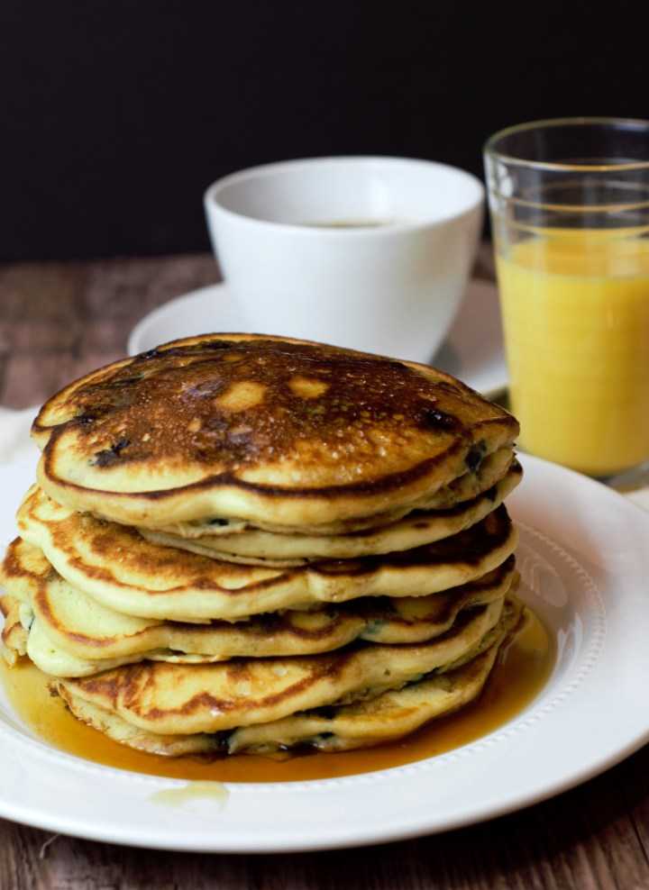 stack of blueberry ricotta pancakes with coffee and juice