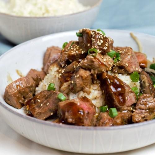 Teriyaki steak over rice in a gray bowl