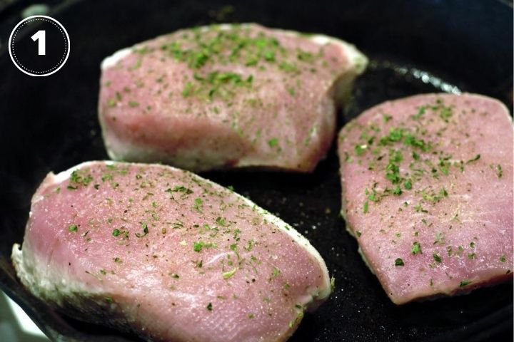 raw pork chops in cast iron pan