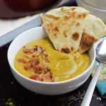 close up soup in bowl with bacon and naan bread