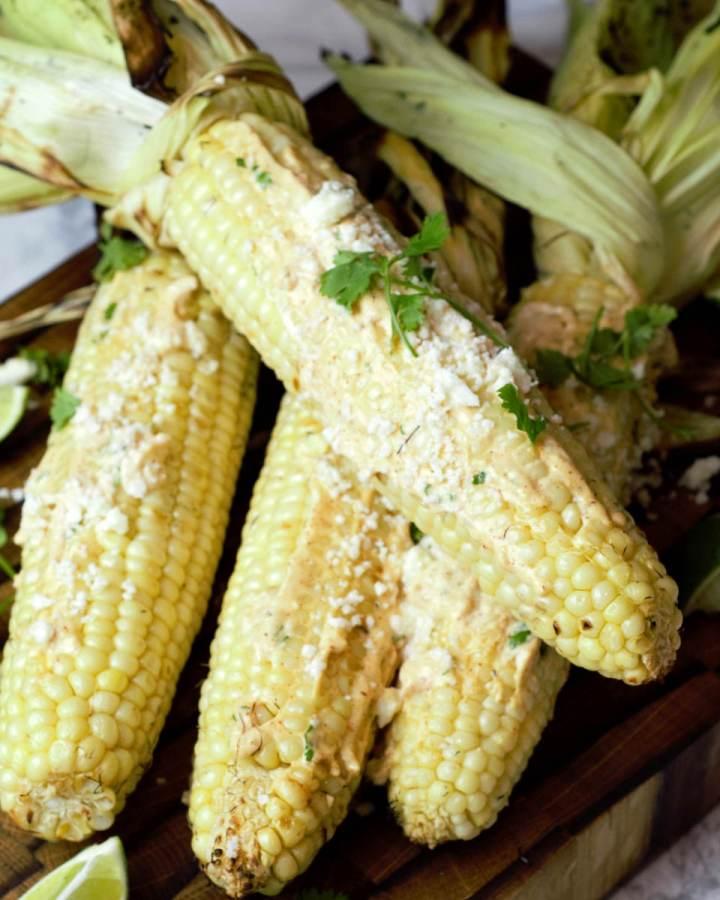 four ears of corn with street corn sauce