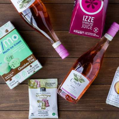 Bottles of Cavit Rose Wine, My/Mo Mochi Ice Cream and other Treats on a Wood Backdrop