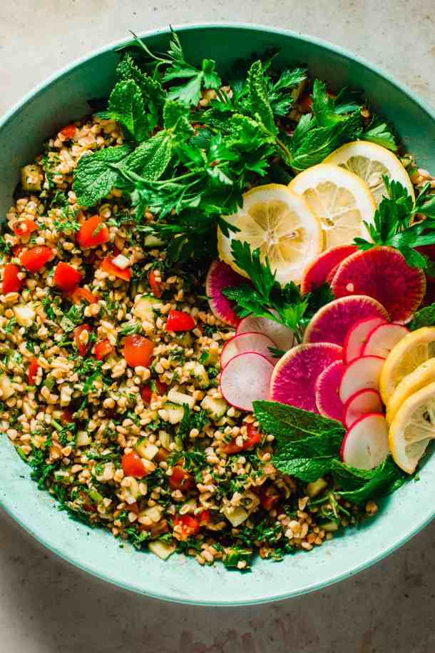 Large bowl filled with bulgur salad and garnished with parsley leaves and radishes