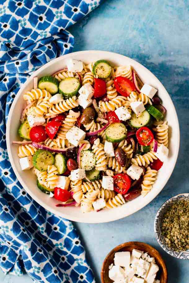 Pasta salad in a white bowl with small bowl of oregano and small bowl of feta cheese