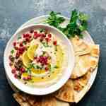 White bowl of pureed eggplant topped with parsley, olive oile, and pomegrante on a white plate with pita bread.