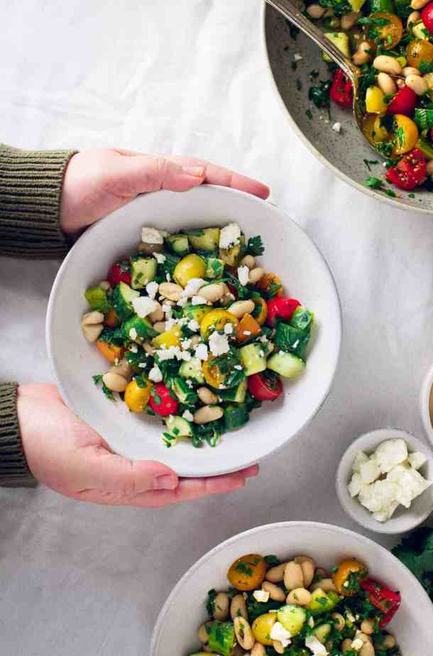 three bowls of simple bean salad: one bowl is being set on the table