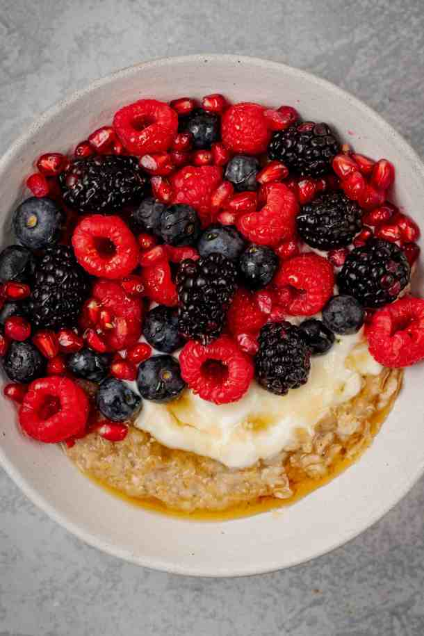 A bowl of oatmeal with yogurt and lots of berries