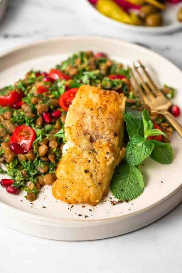 Pan-fried fish and lentil salad on a plate